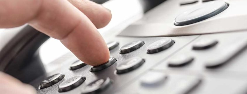 Fingers dialing digits on a phone pad
