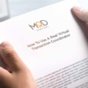 person holding papers that say how to use a myoutdesk real virtual transaction coordinator