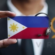 myoutdesk virtual assistant holding up a filipino flag with a headset and myoutdesk logo