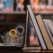 myoutdesk logo in laptop next to books