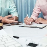 two real estate professionals working together at a table with papers and a gavel