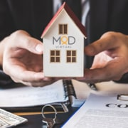 MyOutDesk mortgage virtual assistant holding a model house with a money and contract on table