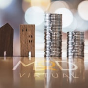 four wooden house blocks next to a stack of silver coins on a desk myoutdesk logo