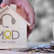 hand holding a wooden house with myoutdesk logo