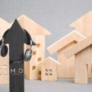 black wooden arrow with myoutdesk logo and set a headphones around other wooden houses