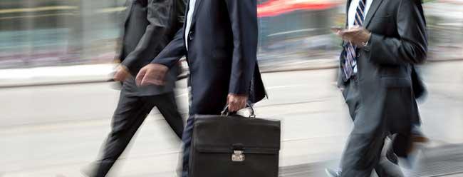 three businessmen walking with a briefcase