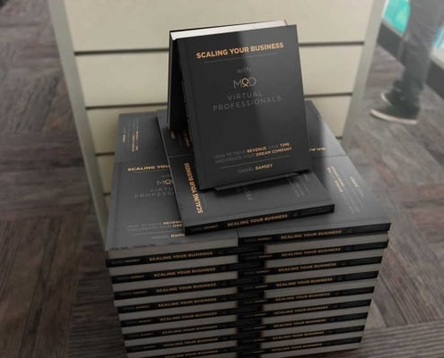 stack of books titled scaling your business with myoutdesk virtual professionals