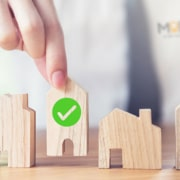 myoutdesk real estate virtual assistant putting a wooden house block with a checkmark down next to other wooden house blocks