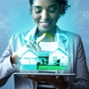 realtor holding a tablet with a virtual house and myoutdesk logo above it