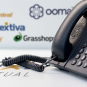 a phone next to myoutdesk logo with vonage ringcentral nextiva grasshopper and ooma in the background