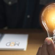virtual assistant holding a lit light bulb in his hand