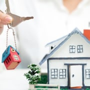 real estate virtual assistant holding up keys with a house keychain next to a model house