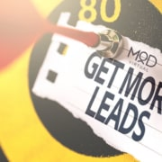 an arrow on a target with a pinned paper that says get more leads