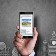 hand holding smartphone with property webpage on it