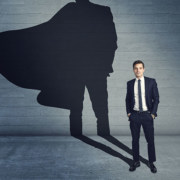 a businessman standing in front of a wall with a shadow of him with a cape