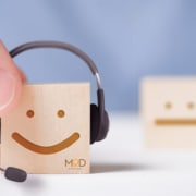 a smiling wooden block with a headset and myoutdesk logo