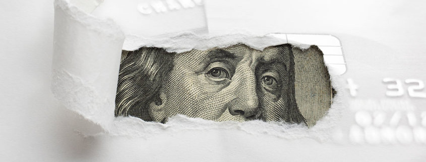 a white paper with a hole ripped open showing a benjamin franklin bill looking through