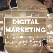 a digital marketing team work together at a conference table with digital marketing graphically in the middle surrounded by virtual logos and charts