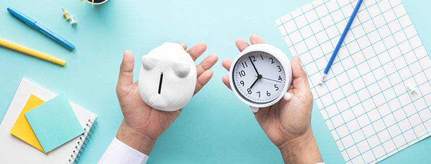 two hands over a desk with a piggy bank in one palm and clock in the other