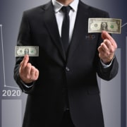 a businessman holding up two one dollar bills with 2020 and 2021 graphics