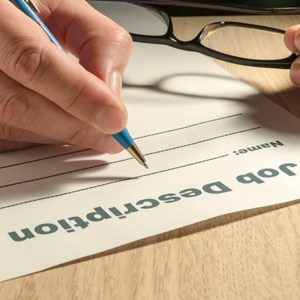 hand with pen filling out a job description for a sales development virtual assistant