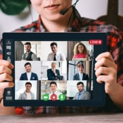 What a virtual assistant looks like remote worker holding up a tablet of a virtual meeting
