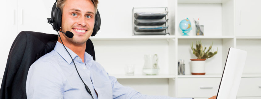 a male virtual assistant smiling at a computer using asana