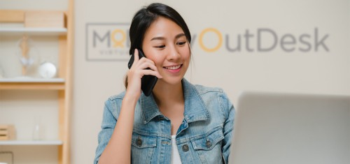 virtual assistant at home calling with myoutdesk logo at the wall