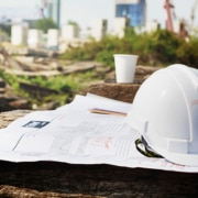 construction site with papers and helmet on wooden platform